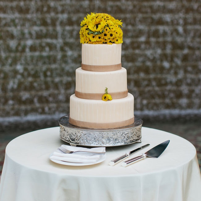 Each layer of the three-tiered, ivory, fondant cake was decorated with clay-colored organdy ribbon and an engraved stripe pattern. A bright yellow bunch of sunflowers in various sizes topped the cake.