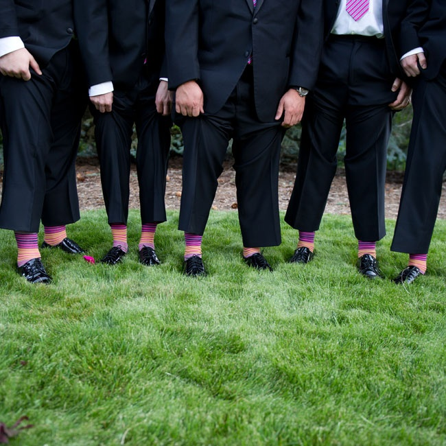 Groomsmen sported matching vibrant pink and orange striped socks with their dark, formal suits.