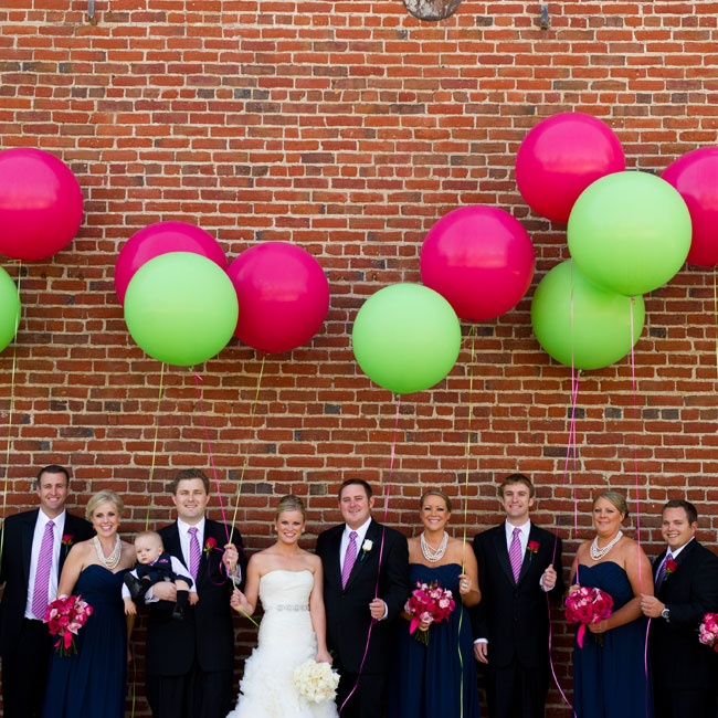 The wedding party held bright, colorful weather balloons in pink and lime green as contrast to their darker, more formal attire.