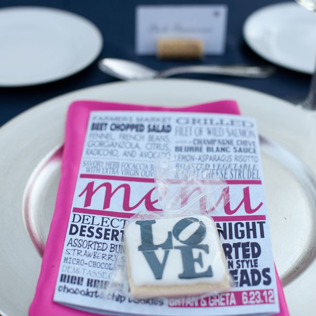 "The couple's menu cards made use of playful typography in bright pink and black and played into their edible favors: a cookie with the word ""Love"" written on it."