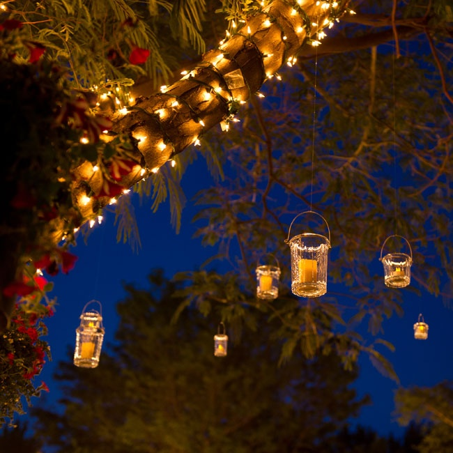 The trees at the reception were wrapped in Christmas lights and decorated with hanging candles.