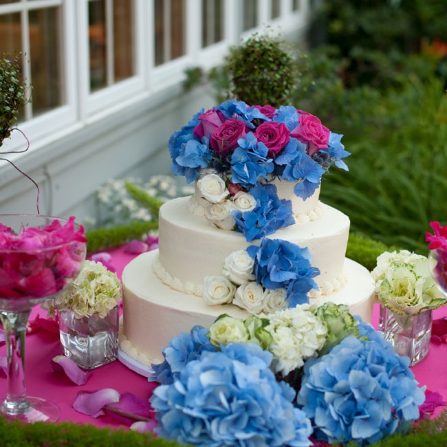 The couple chose a traditional, tiered, ivory round cake and brightened it up with cobalt blue and pink flowers.