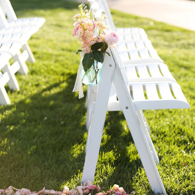 Blue Mason jars were filled with pink and peach stock flowers and roses during the ceremony.