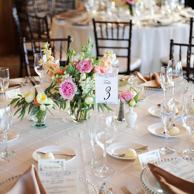 The couple combined neutrals with their pastel color palette at the reception with ivory linens and romantic flower arrangements.