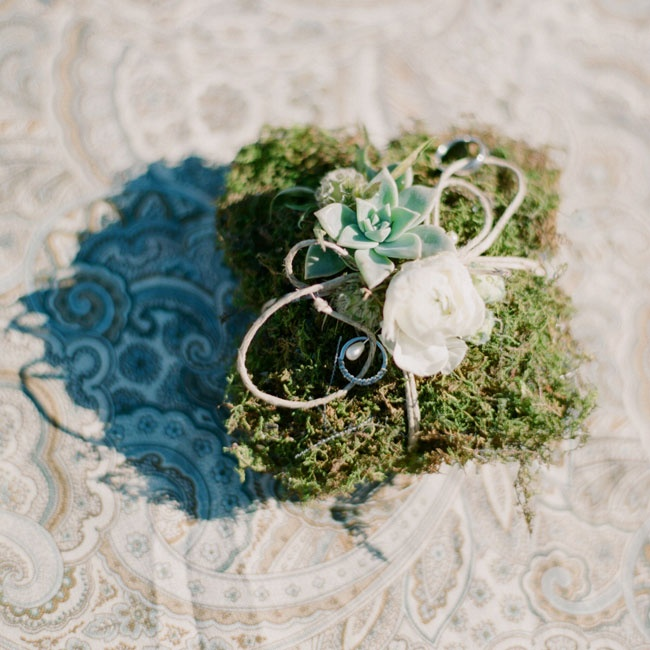 The rings were carried down the aisle on a moss ring pillow that was decorated by rustic elements like twine, succulents, and a scabiosa pod.