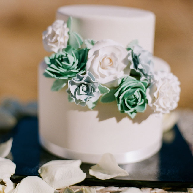 Though the couple didn't host a ceremony, they did have a small cutting cake. The two-tiered fondant cake was decorated with white satin ribbon and a cascade of sugar flowers and succulents in cool pastel shades that matched Jo's bouquet.