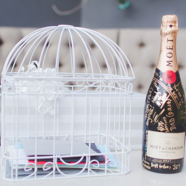 A table was set up with a closed bottle of Moet champagne for the guests to inscribe with their best wishes to the couple, as well as a birdcage for those who wished to insert a more lengthy letter for My-Lee and James.