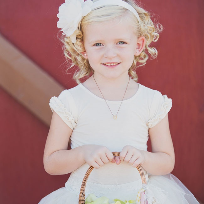 The flower girl an ivory tee with ruffle cap-sleeves and full tulle skirt. A flower headband in a similar shade finished off the look