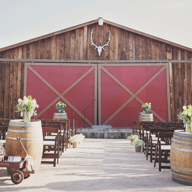 A rustic barn was the backdrop for the ceremony. The entrance and the altar were decorated by large wine barrels topped with arrangements of white peonies, lush greens and bright billy balls.