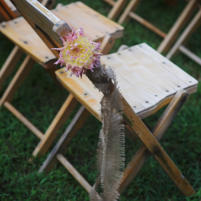 The chairs at the ceremony were decorated with a light pink and yellow dahlia and a simple strand of burlap hanging down from them.