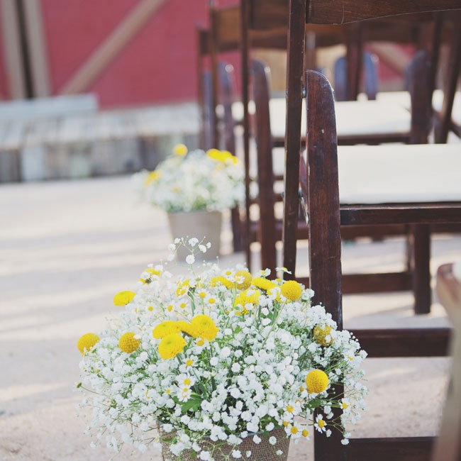 Burlap wrapped pots with bright bunches of yellow button mums, daisies and baby's breath that had a just-picked feel.