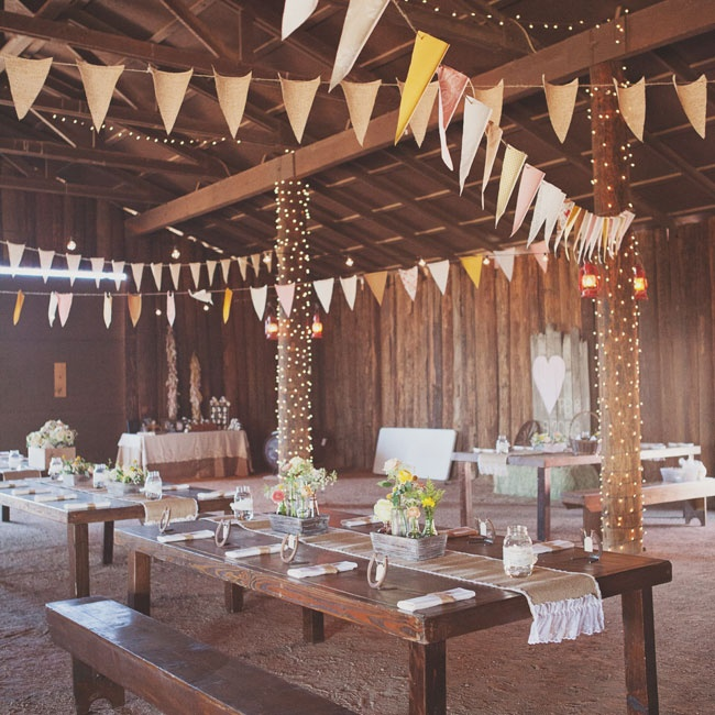 The newlyweds and their guests gathered in the Desert Foothills barn for the reception. Long farm tables were decorated with rustic linens and simple, yet cheerful floral arrangements. Strings of fairy lights and bunting hung from the barn rafters for a festive touch.