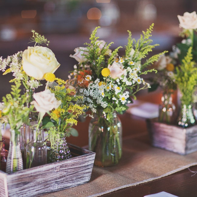 Distressed wooden boxes displayed bud vases filled with bright yellow and white flowers, like roses, billy balls, daisies and queen anne's lace.