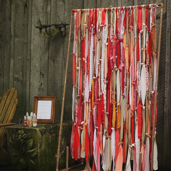 An assortment of fabric in red, orange and peach coloring was knotted together by the bride and her family to create hanging strands as a backdrop for guests to take pictures in front of during the reception.