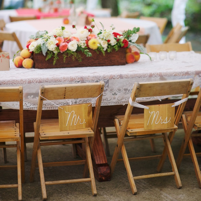 "With cute ""Mr."" and ""Mrs."" signs hanging from Jessica and Dan's chairs, the main bridal table had a lace tablecloth runner that was made by the mother of the bride and featured a garden style floral arrangement of peonies and roses in a long wooden flower box."