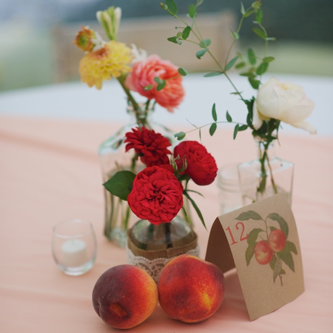 The guests' tables at the reception featured table name cards with peaches, instead of the strawberry design that was used on the bride and groom's table, as well as small vases that were filled with a few ranunculuses, dahlias and peonies and were surrounded by loose peaches.