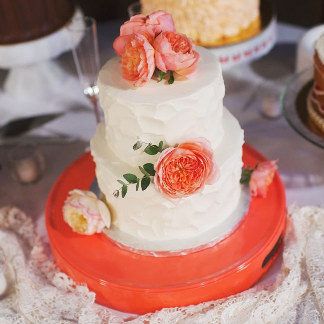 Jessica and Dan's wedding cake was a two tiered white cake with peach peonies on top of it that sat on a peach colored cake stand. It was displayed on the dessert table along with various other cakes for guests to choose from.