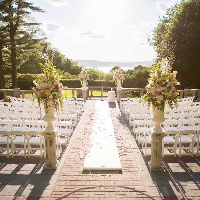The ceremony took place outside of the venue, overlooking the Hudson River. The ceremony decorations were romantic; there was a white aisle runner with pink rose petals strewn down it and large floral arrangements at the beginning and end of the aisle.