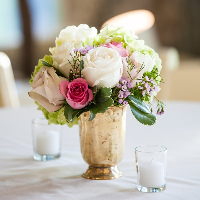 Small floral centerpieces were displayed on the tables in golden vases. The flowers that made up the centerpieces were peonies, roses, viburnum and various others.