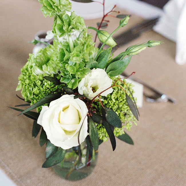 Textured green and white centerpieces with roses, hydrangeas and mums sat atop burlap table runners for sophisticated look.