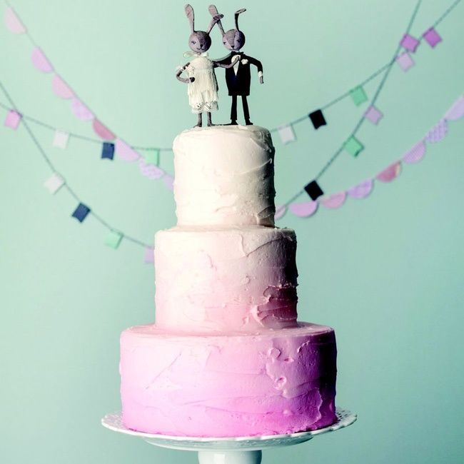 A pink ombre buttercream cake topped with a rabbit cake topper by BHLDN.