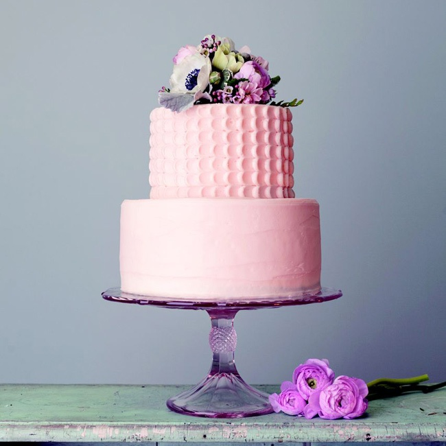 A simple pink buttercream cake on a pink cake stand is perfect for a wedding or bridal shower.