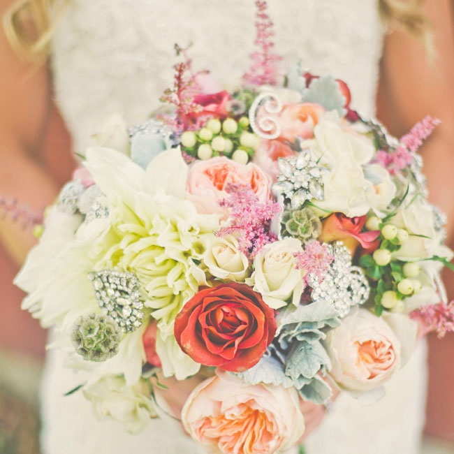 Calli arranged her bridal bouquet herself with flowers she bought wholesale. The bouquet was filled with roses, peonies, astilbe, dahlias and scabiosas in a mix of bright colors and accented with crystal brooches.