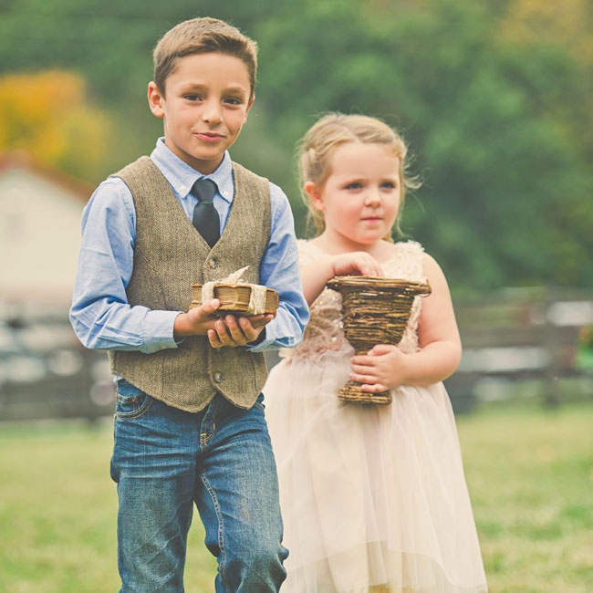 The ringbearer for blue jeans, a blue button down shirt and tweed vest for a casual look, while the flower girl wore an airy neutral dress with tulle and sequin accents.