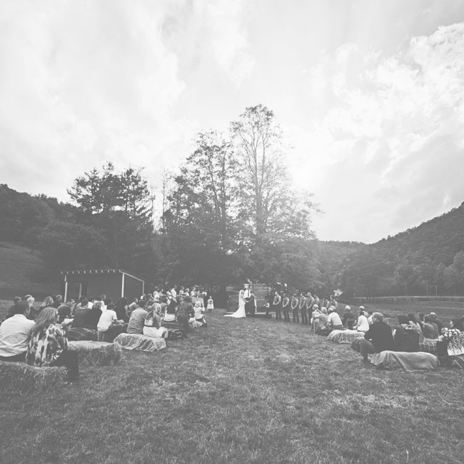 The ceremony took place outdoors with guests seated on haystacks covered in rustic, flannel blankets.
