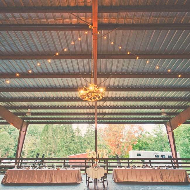 "An open-air corral with a covered roof was the site of the reception. Strings of bistro lights, an antler chandelier and marquee lights spelling out ""Love"" added warm ambient light to the space."