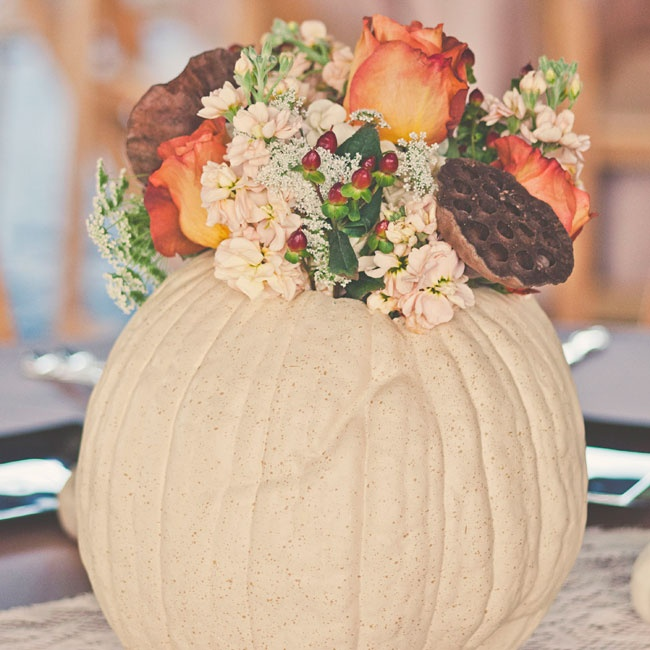 White pumpkins filled with orange roses, peach stock flowers, hypernicum berries and lotus pods came together to create a rustic look for the reception centerpieces.
