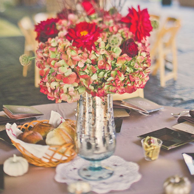 Bright red flowers including zinnias, hydrangeas and roses accented by scabiosa pods were arranged in silver vases surrounded by small white pumpkins for an elegant, autumnal look.