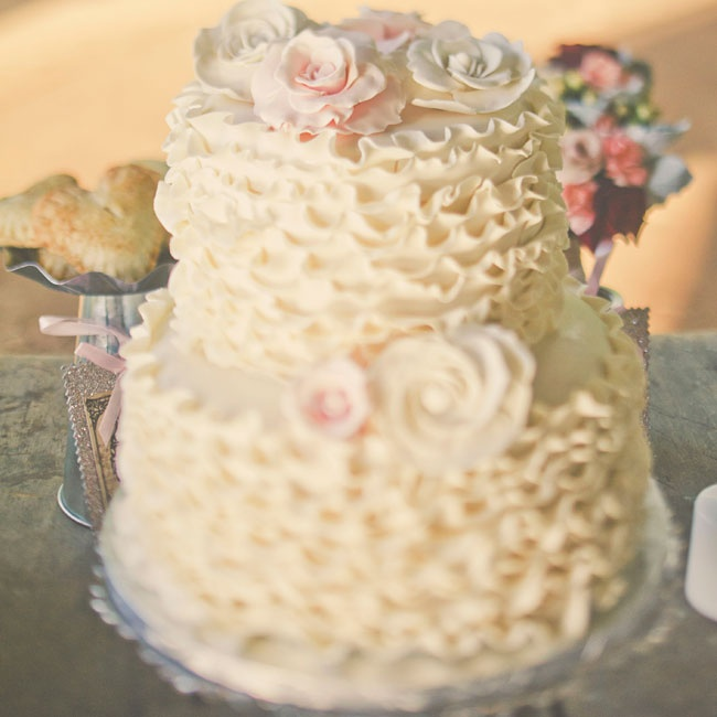 The two-tier ivory cake was covered in fondant ruffles and muted pastel sugar roses.