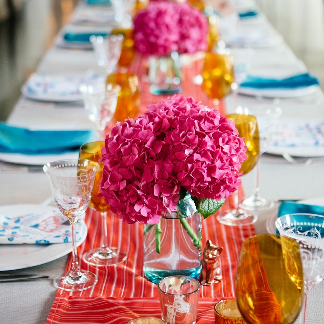 The long farmhouse style tables had a cheerful vibe with bright linens in blues and reds, as well as arrangements of vibrant pink hydrangeas and tinted glasses.