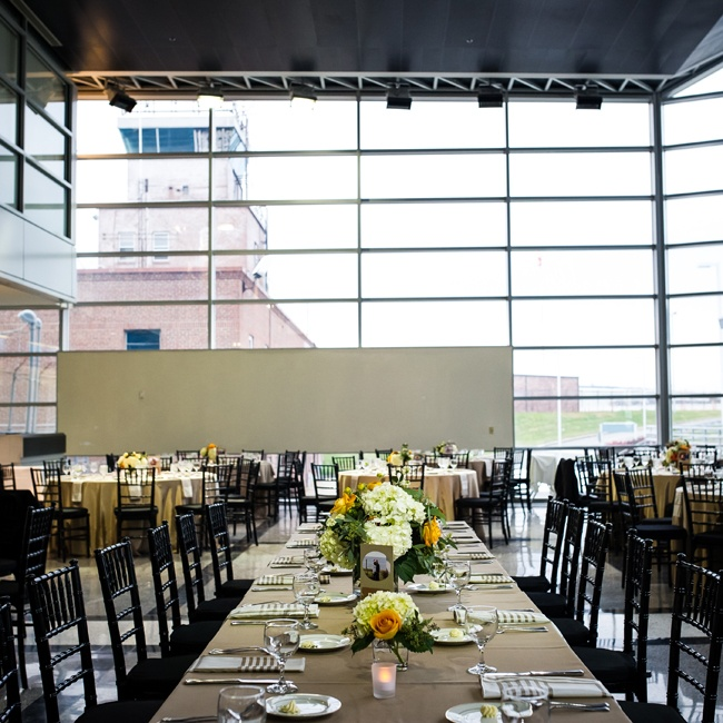 The couple transformed this regional airport setting into an elegant ballroom with long tables, dark Chiavari chairs and bright centerpieces.