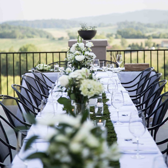 The couple held an intimate reception at Delaplane Cellars overlooking the stunning vineyards and mountainous landscape. The couple went for a sophisticated look using white, floral centerpieces and white linens with a green moss table runner.