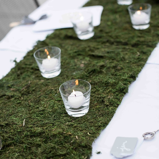 Mossy table runners scattered with votive candles gave an earthy touch to the table decor.