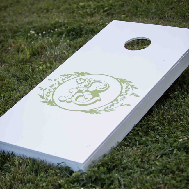 The couple and their guests played lawn games like cornhole during cocktail hour. The cornhole boards were painted white and displayed the couple's monogram.