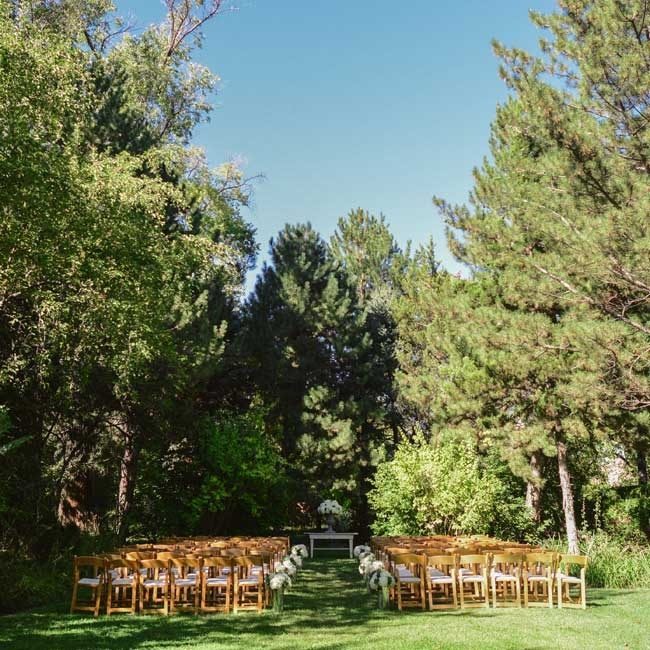 The ceremony was in a clearing in a large forest and was accented with light wooden chairs and simple floral aisle markers.