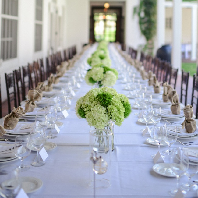Guests ate at one long table during the reception dinner, which was decorated with green and white floral arrangements.