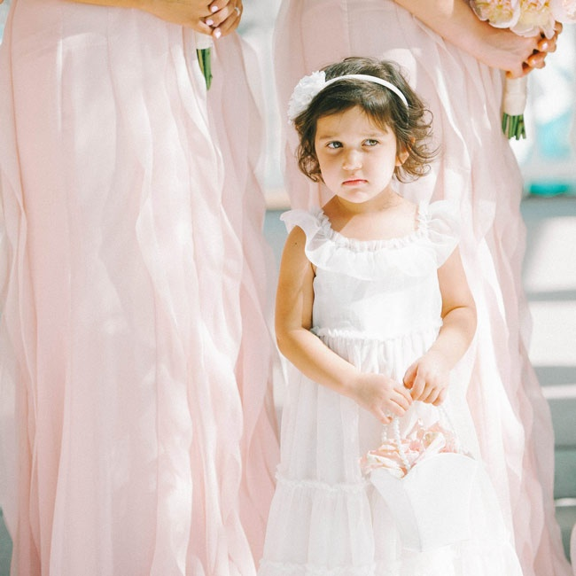 The flower girl wore a flowy, classic white dress with a feminine flutter cap sleeve and accessorized with a white rosette headband.