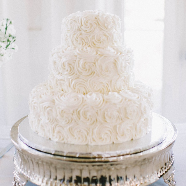 The couple chose a traditional white, round wedding cake with three textured, rosette tiers.