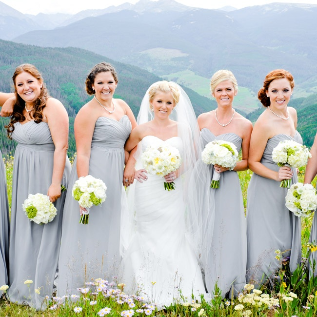 The bridesmaids wore long, strapless, chiffon dresses in a pale gray color that complemented the wedding's color palette. The draped sweetheart bodices and light flowy fabric gave the dresses a romantic look. The girls accessorized with simple strands of pearls for a simple, classic look.