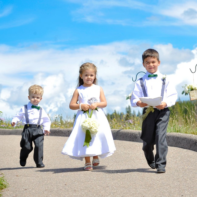 The flower girl wore a handmade white dress with gray, crystal embellishments, while the boys wore dark gray trousers with white dress shirts, green boy ties and gray suspenders.