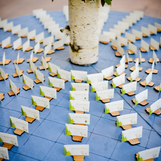 The escort cards used the same Vail-themed motif as the couple's invitations and were set in wooden Wisconsin-shaped holders.