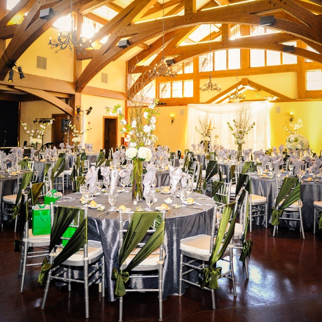 Molly and Nick decorated the Donovan Pavilion in a dark gray and green color palette. The dark gray textured linens were laid on the tables with green napkins adding a pop of color. Silver chiavari chairs with ivory cushions were draped with green satin fabric tied into a bow. Tall white floral arrangements, some with birch accents, were the center ...