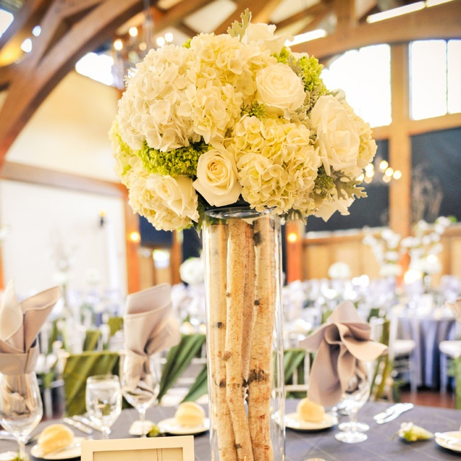 The couple chose two different styles for the centerpieces. One included small birch branches in tall hurricane vases topped with lush white and green arrangements of roses, and hydrangeas. The second style, also included tall hurricane vases filled with willow branches and hydrangeas.
