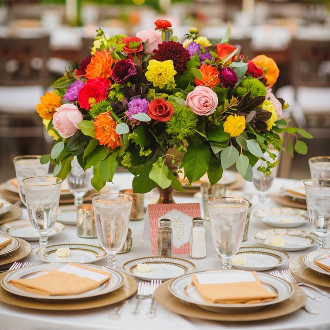 Lush greenery and bright blooms like roses, ranunculuses and dahlias were arranged in elegant golden bowl vases that complemented the timeless sophistication of each tablescape.
