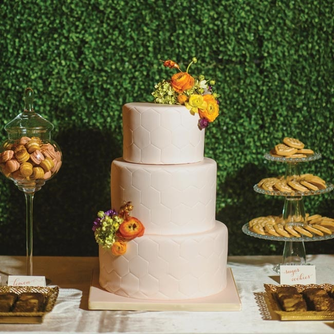 As a nod to David's beekeeping pass time, the couple had each layer of their fondant cake designed in a honeycomb pattern. Bright ranuncluses, Carly's favorite flower, in warm oranges and yellows added a fresh pop of color to the ivory cake.