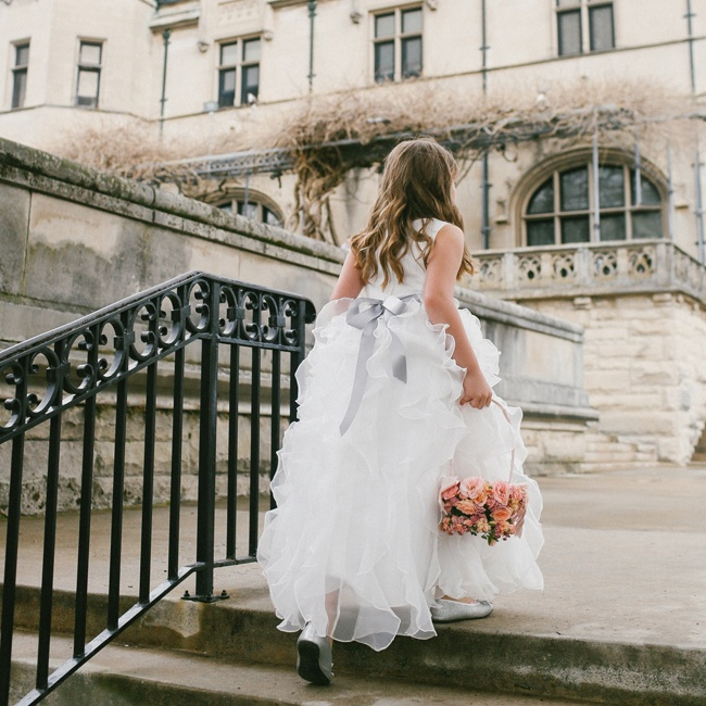 Flower girls wore matching ruffled Watters dresses and accessorized with slate sashes that matched the bridesmaid gowns.